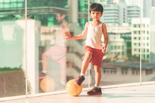 フットボール選手の少年は部屋でボールを踏んでいます。