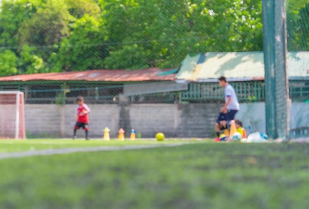 背景にぼやけている子供のトレーニングのためのサッカーアカデミーフィールド