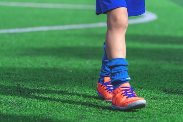 サッカー場のトレーニングコーンでトレーニングサッカーブーツを持つ子供の足