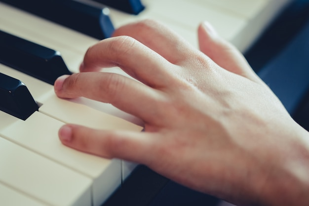 音楽のコンセプトのピアノのキーを押すと子供の手