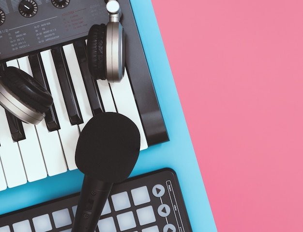 黒いマイクとテーブルトップ上のヘッドフォンコピースペースの青とピンクの背景を表示します。