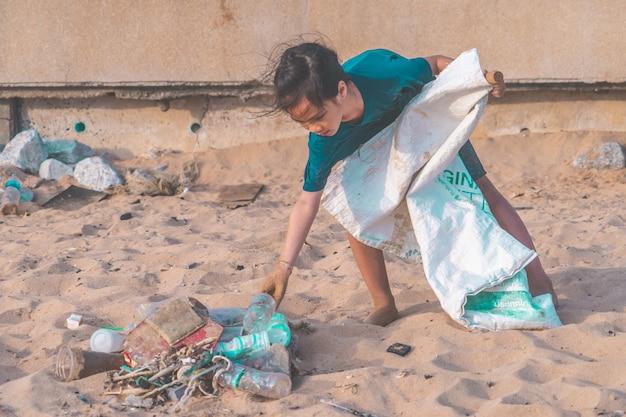 Дети собирают пластиковую бутылку и мусор, которые они нашли на пляже для концепции экологической очистки