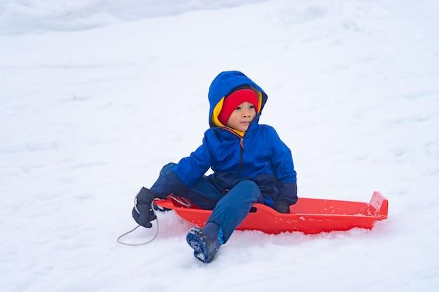 ガラ湯沢スキー場の小さな男の子が雪そりを滑り降りる