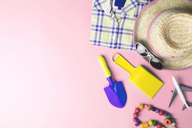 ピンクのパステルカラーの背景に男性の休暇ビーチファッション夏の休日アクセサリーのトップビュー