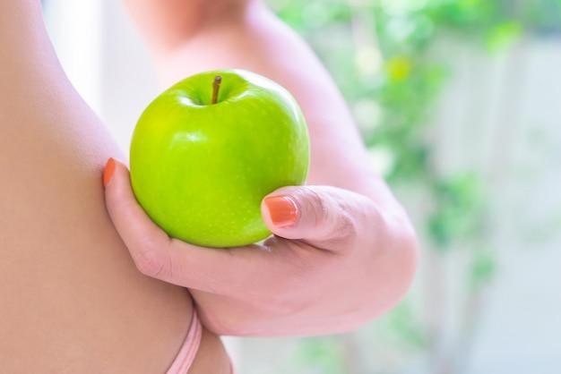 女性の手は、健康な体のケアの概念のために彼女の体の横にある彼女の手にリンゴを保持しています。