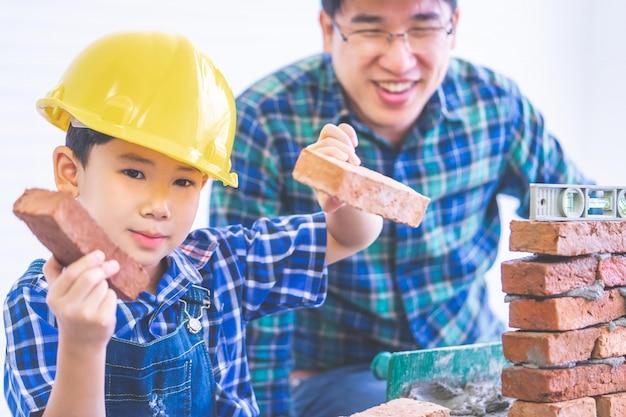 Азиатский мальчик учит, как построить кирпичную стену от своего отца строителя, отец инженера учит своего сына в ремонте дома для концепции образа жизни семьи.