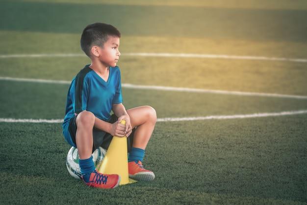 Мальчик отдыхает на футбольном поле