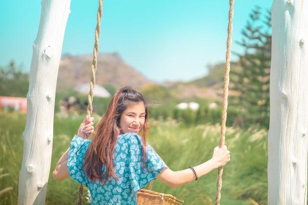 Счастливая красивая азиатская женщина имея время ослаблять на качании в поле природы для образа жизни счастья природы