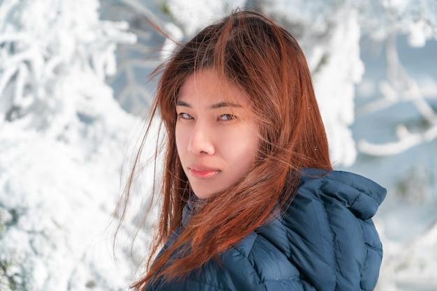 雪スキーリゾートで美しい肌の顔を持つ冬のファッションの服と美容魅力的な女性