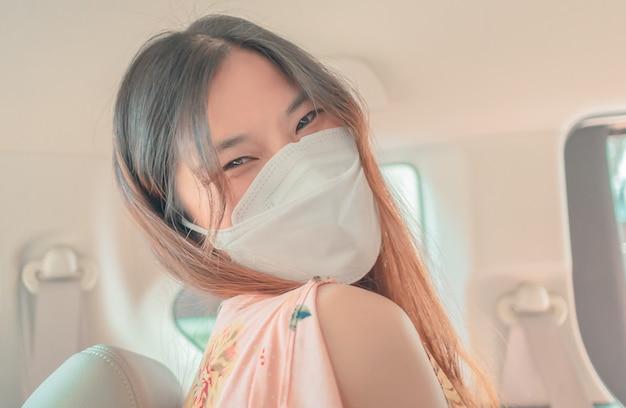 Счастливая азиатская женщина внутри автомобиля носит хирургическую маску с улыбкой.