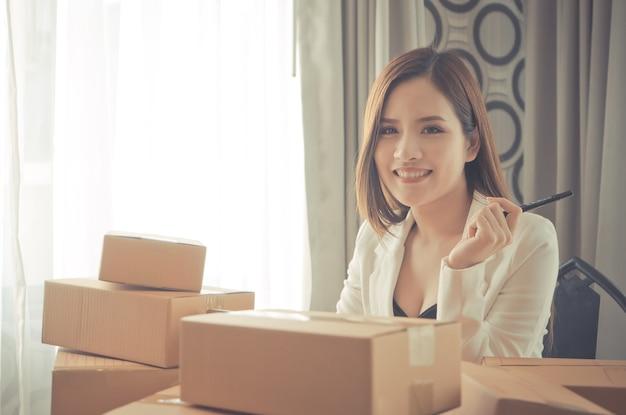 Счастливый ставить бизнес-леди, сидя в стол, полный коробки доставки