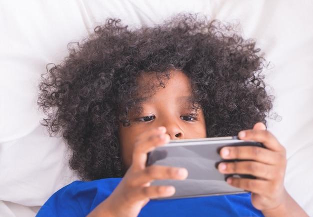 小さなアフリカの子供がベッドでスマートフォンで遊んでいる