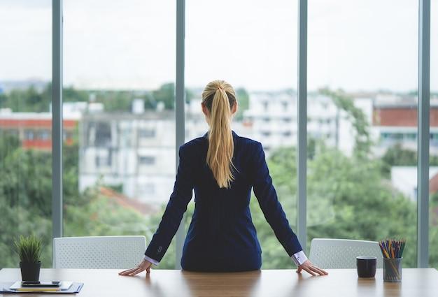 女性のビジネスの女性は成功のための窓を探しています