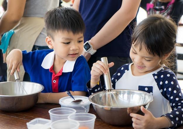 Азиатский ребенок и семья учатся делать мороженое в кулинарном классе.