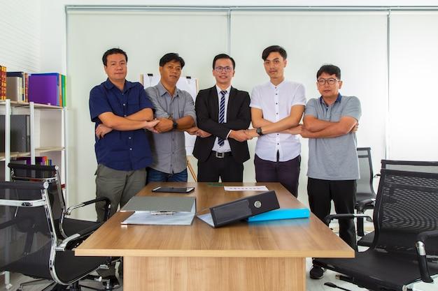 参加し、オフィスでチームワークを示す手を保持しているビジネス人々のグループ。