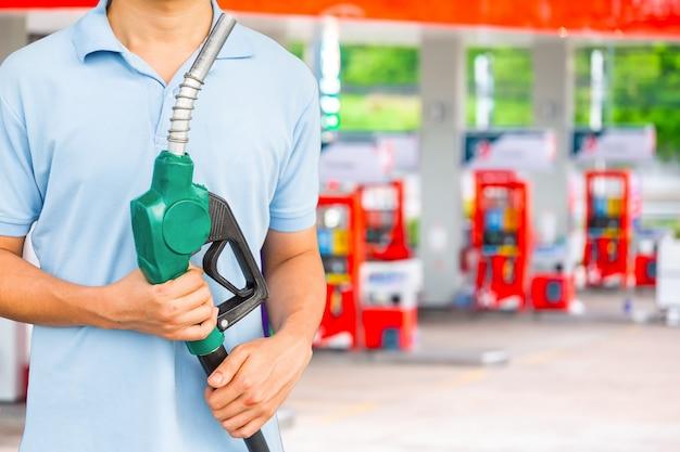 人はガソリンスタンドで車に燃料を入れるために燃料ノズルを持っています。