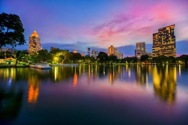 Вид на озеро парка лумпини в центре столицы таиланда со зданиями в бангкоке