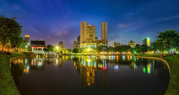 日没時の前景に公共公園エリアがあるバンコクのビジネス地区