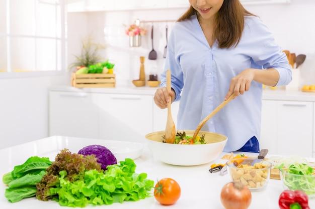 若い女性が台所で料理。健康食品-野菜サラダ。ダイエット。ダイエットのコンセプト。健康的な生活様式。自宅で料理。食べ物を用意します。