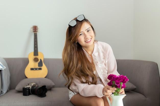 Счастливая азиатская женщина украшая живущую комнату с красивыми цветками дома.