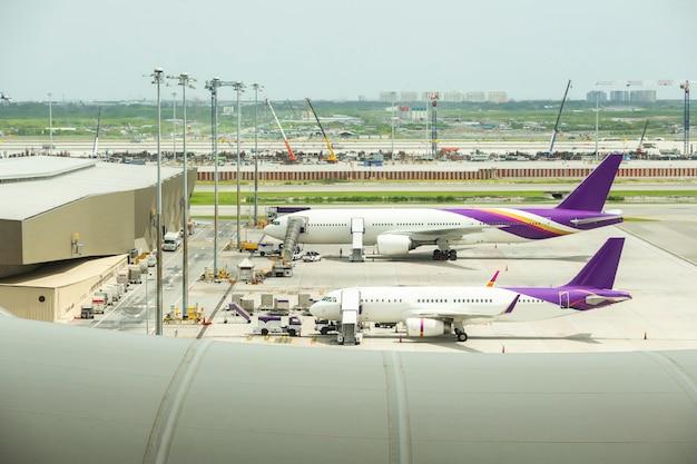 ゲートに航空機があり離陸する忙しい空港