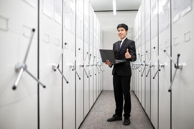 Менеджер банка с помощью ноутбука в раздевалке серверной комнаты