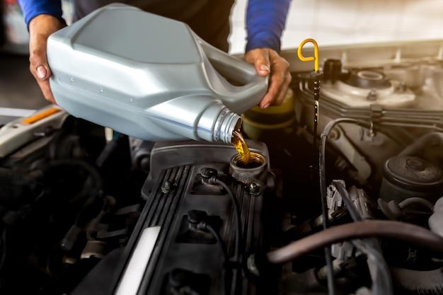 自動車修理工がメンテナンス修理サービスステーションでエンジンに新鮮なオイルを交換して注ぐ。