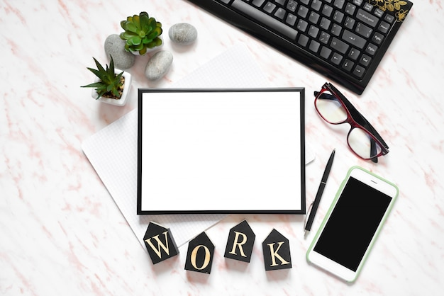 フラットレイアウトのオフィスの大理石の机、電話、キーボード、ノート、テキスト領域の背景のフレーム