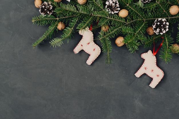 クリスマスの暗い休日の背景、手作りおもちゃの馬、トウヒの枝、松ぼっくりと組成で設定自然装飾