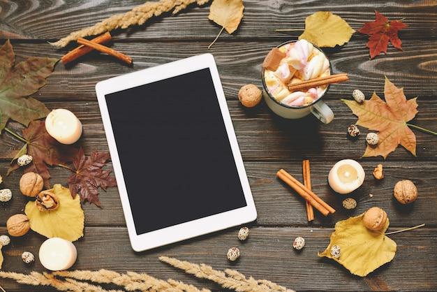 乾燥秋の葉、マシュマロ、ナッツ、シナモン、格子縞、タブレットとりんごとココアのマグカップ