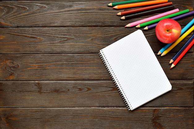 学校のコンセプトに戻るノートブックを開くと木製の背景に色鉛筆でアップル