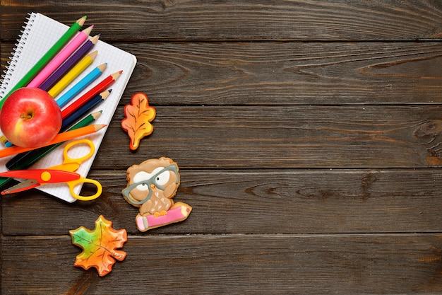 色鉛筆、赤いリンゴとジンジャーブレッドの木製のテーブルの上の学校概念の背景に戻る