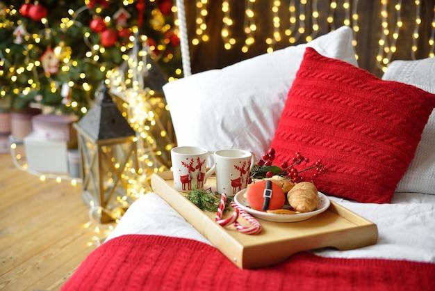 Завтрак в постель, поднос с чашкой кофе и круассаном. современный интерьер спальни. романтический утренний сюрприз.