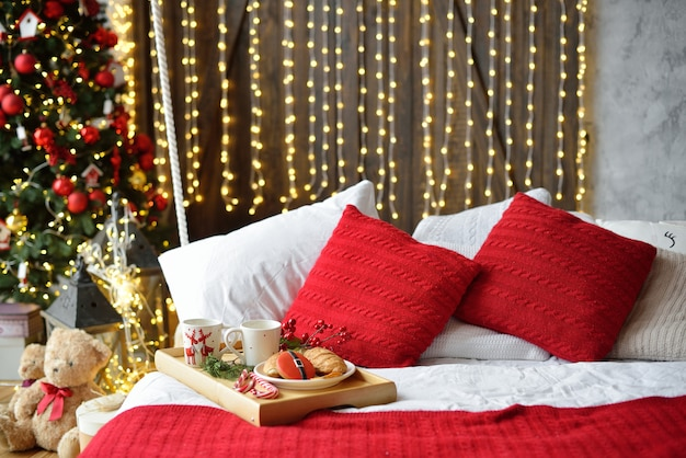ベッドで朝食、コーヒーとクロワッサンのトレイ。モダンなベッドルームのインテリア。ロマンチックな朝の驚き。