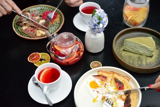 パンケーキ、紅茶と朝食のテーブルセッティング。カップルが食べています