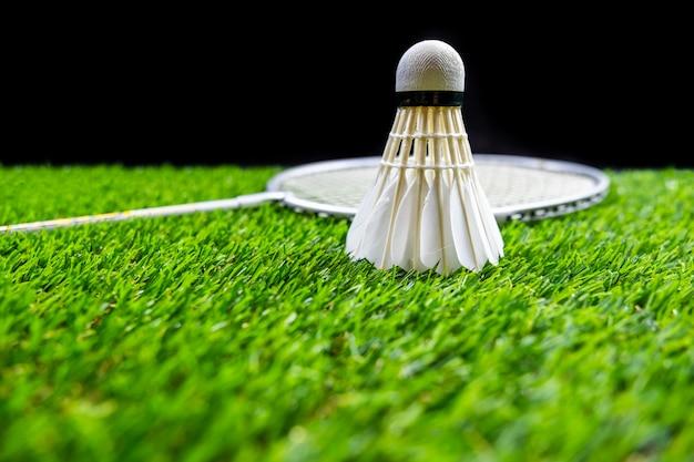 バドミントンボールと黒の背景で芝生の上のラケット
