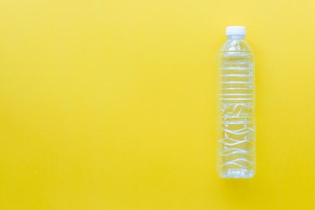 黄色の背景にプラスチックボトルをリサイクル