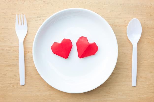 白い皿、愛とバレンタインの日の概念にカップル赤い折り紙ハート