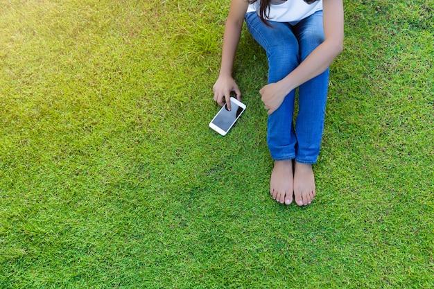 ソーシャルメディアでリラックスするための芝生の上のモバイルのスマートフォンをしている女の人