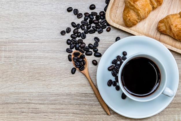 コーヒー豆と木製のテーブル、朝食のコンセプトにクロワッサンと白いカップでコーヒー