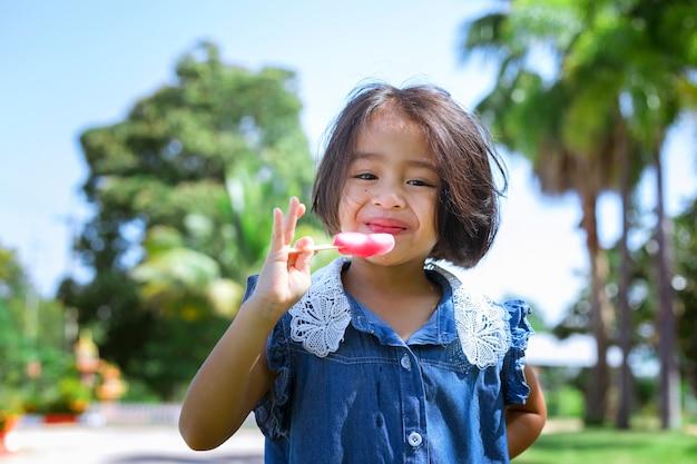 日没でアイスキャンディーを食べるかわいい女の子