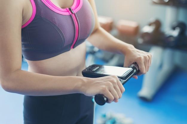 美しい女の子は、ハードワークアウト後の検査で体重をチェックする