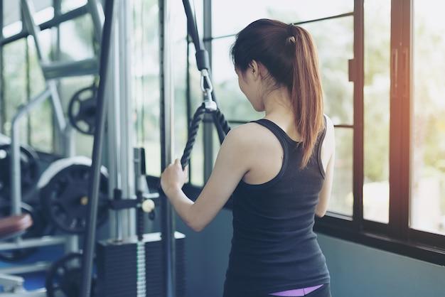 美しい女の子は公共のジムで筋肉を強化するためにロープを引っ張って練習