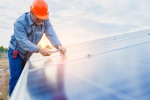 Молодой человек ремонтирует солнечную панель на станции.