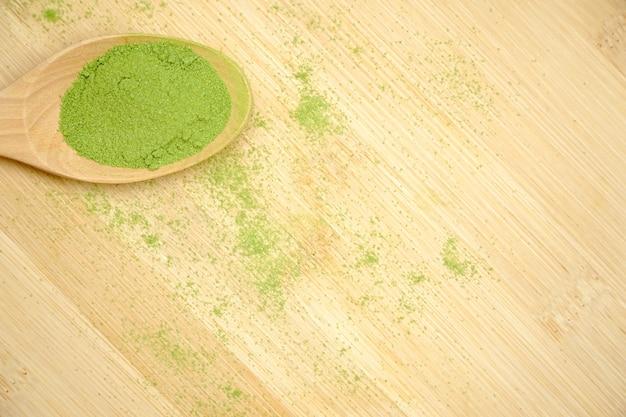 木製テーブル上の木スプーンの緑茶抹茶粉のトップビュー。