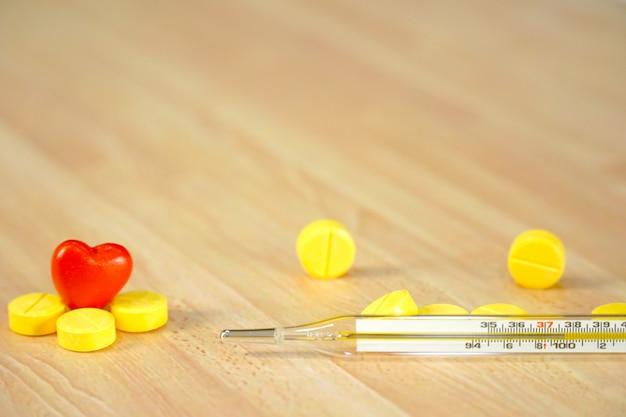 Стеклянный термометр с желтыми лекарствами и мини-красное сердце на деревянный стол.
