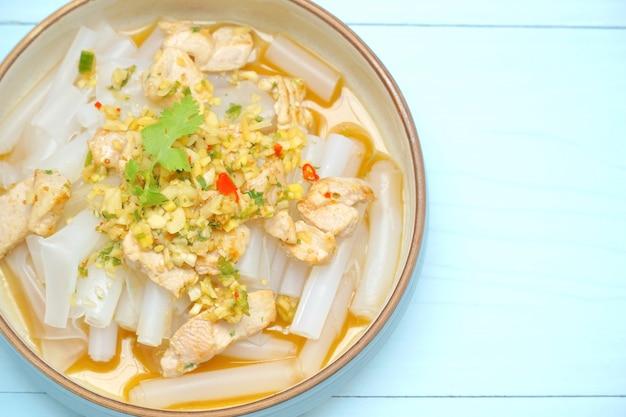 青いテーブルに豚肉とサワーソースで上海麺の炒め