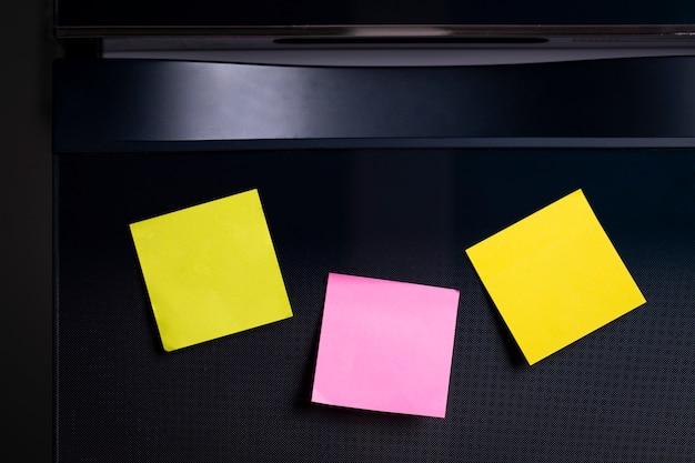 Пустой лист бумаги для заметок на двери холодильника.