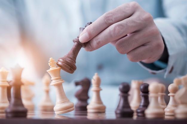 Бизнесмен играет с игрой в шахматы в соревновательной игре успеха, концепции стратегии и успешного управления или руководства