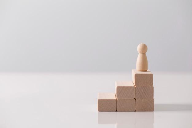キャリア成長やビジネスの成功の概念としてウッドブロックの最高点に立っているビジネスマン。